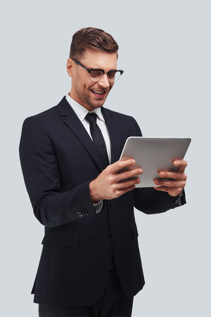 Confident and smart. Handsome young man using digital tablet and smiling while standing against grey background