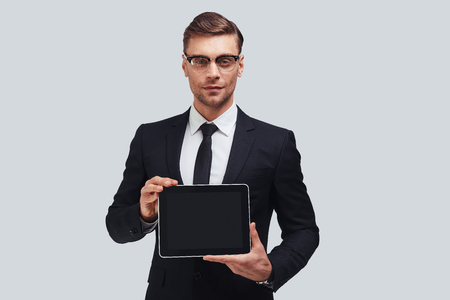 Copy space on his digital tablet. Good looking young man in full suit holding digital tablet and looking at camera while standing against grey background