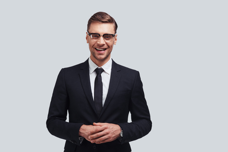Confident business expert. Handsome young man in full suit keeping hands clasped and looking at camera with smile while standing against grey background Stock Photo