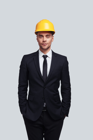 Safety comes first. Good looking young man in hardhat keeping hands in pockets and looking at camera while standing against grey background