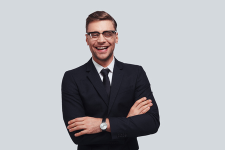 Used to look perfect. Handsome young man in full suit keeping arms crossed and looking at camera with smile while standing against grey background