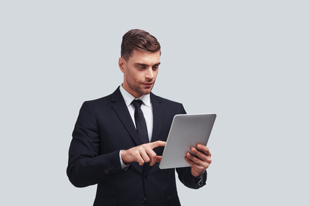 Achieving best results. Handsome young man using digital tablet while standing against grey background
