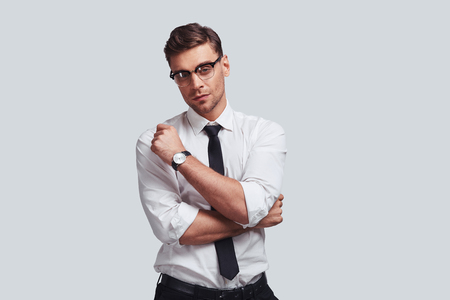 Thoughtful man. Good looking young man looking at camera while standing against grey background