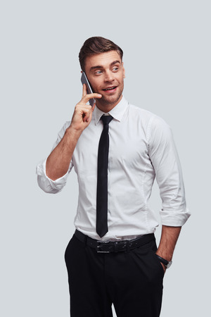 Important business talk. Handsome young man talking on smart phone and looking away with smile while standing against grey background