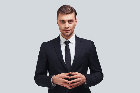 Young perfectionist. Handsome young man in formal wear keeping hands clasped and looking at camera with smile while standing against grey background