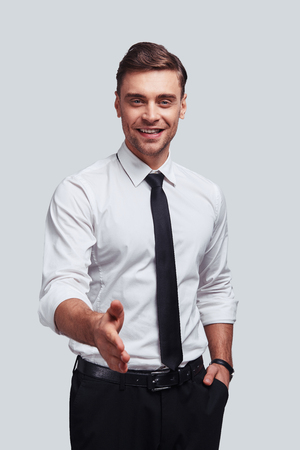 Welcome on board! Good looking young man greeting you and smiling while standing against grey background Stock Photo