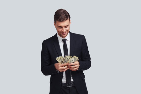 Always in profit. Good looking young man in full suit counting money and smiling while standing against grey background