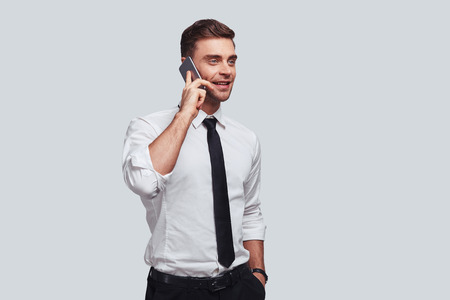Pleasant business talk. Handsome young man talking on smart phone and looking away with smile while standing against grey background Stock Photo