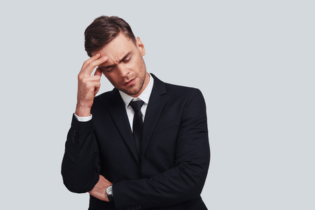 Feeling pain. Frustrated young man in full suit touching his head with hand while standing against grey background