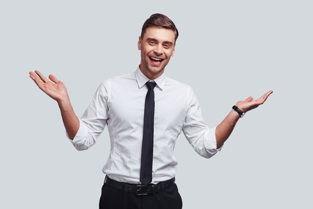You are welcome! Good looking young man keeping arms outstretched and smiling while standing against grey background