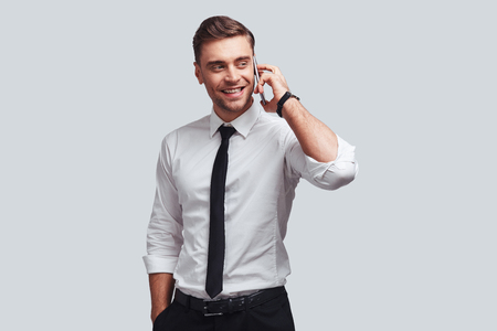 Talking with client. Handsome young man in shirt and tie talking on smart phone and looking away with smile while standing against grey background Stock Photo