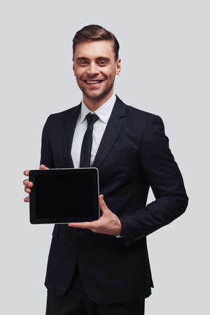 Using modern technologies. Good looking young man in full suit holding digital tablet and looking at camera while standing against grey background Stock fotó - 102236112