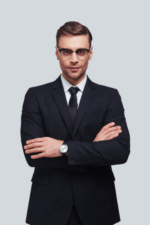 Perfect man. Handsome young man in full suit keeping arms crossed and looking at camera while standing against grey background Stock Photo