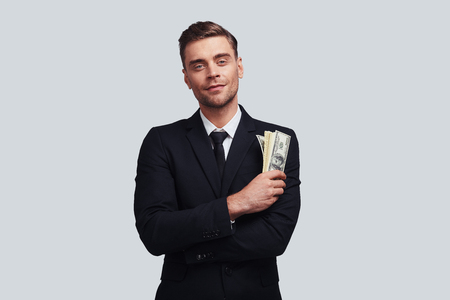 Make money now! Good looking young man in full suit smiling and holding a paper currency while standing against grey background Stock Photo