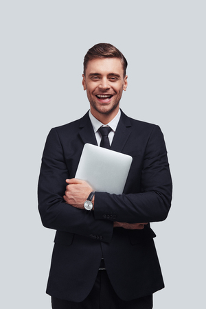Young business professional. Handsome young man carrying digital tablet and smiling while standing against grey background Stock fotó