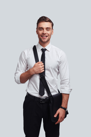 Confident manager. Good looking young man carrying bag and smiling while standing against grey background Stock Photo