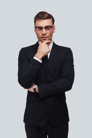 Lost in thoughts. Serious young man in full suit keeping hand on chin and looking at camera while standing against grey background Stock Photo