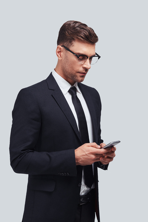 Another business message. Handsome young man using his smart phone while standing against grey background