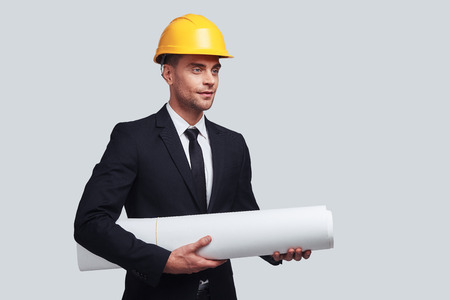 Young architect. Good looking young man in hardhat carrying blueprint and looking away while standing against grey background