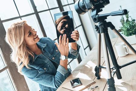 Succesvolle blogger. Mooie jonge vrouw in vrijetijdskleding met digitale tablet en glimlachen tijdens het opnemen van video Stockfoto
