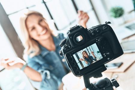 Filmen. Mooie jonge vrouw in vrijetijdskleding glimlachen tijdens het opnemen van video