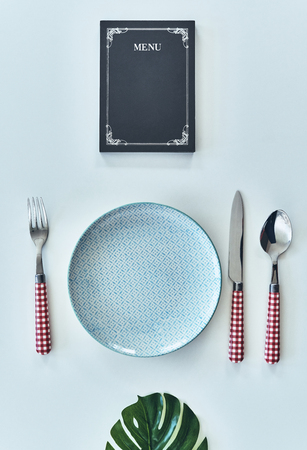 Perfect serve. High angle shot of empty plate, fork, spoon, knife closed menu lying against white background