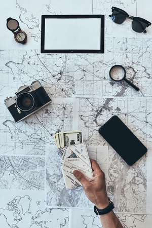 Preparing to travel. Close up top view of man holding passport and money with smart phone, sunglasses, photo camera, compass, magnifying glass lying on map around Stock Photo