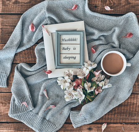 Cozy concept. High angle shot of sweater, flowers, cup of coffee and photo frame on wooden desk Imagens