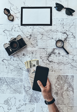 Do not forget! Close up top view of man holding smart phone, passport and money with sunglasses, photo camera, compass, magnifying glass lying on map around