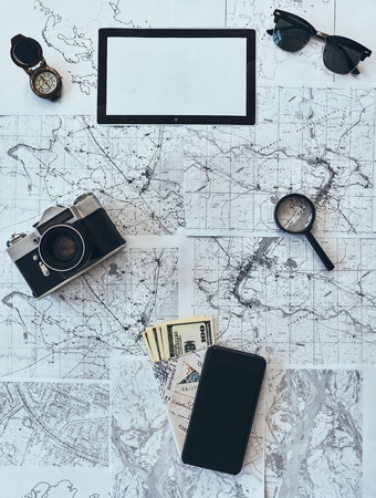 Just travel. High angle shot of sunglasses, photo camera, compass, magnifying glass, smart phone, passport and currency lying on map Stock Photo