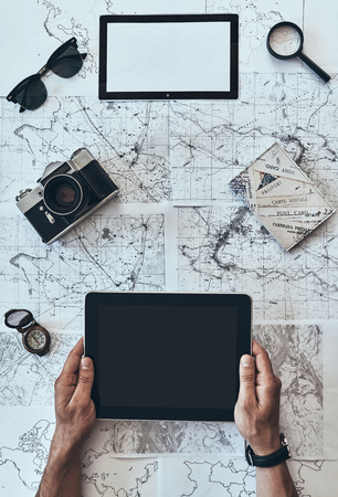 Ready to travel. Close up top view of man using digital tablet with sunglasses, photo camera, compass, magnifying glass and passport lying on map around