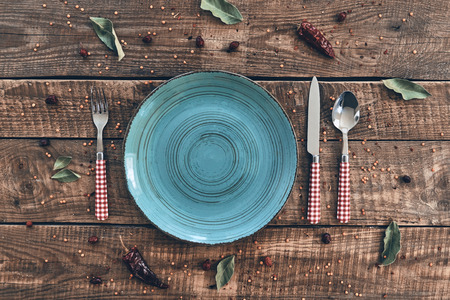 Lunch time. High angle shot of empty plate, fork, spoon, knife lying on rustic table