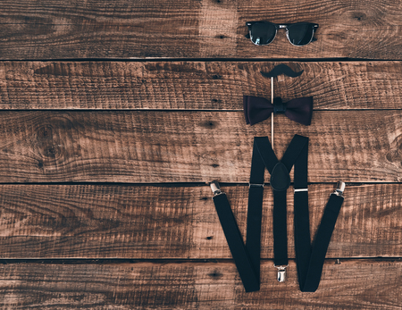 Pure elegance. High angle shot of suspenders, prop, bow tie and eyewear lying on wooden desk