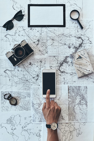 I want to visit every place. Close up top view of man using smart phone with sunglasses, photo camera, compass, magnifying glass and passport lying on map around