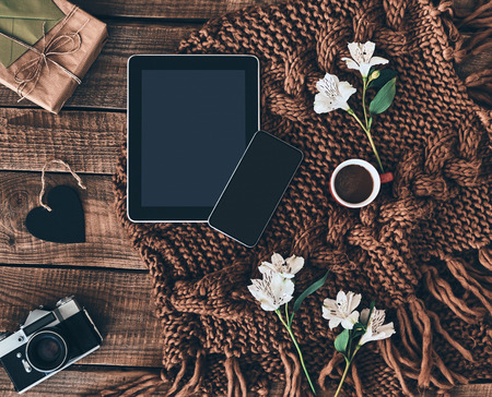 Modern technologies. High angle shot of knitted scarf, flowers, cup of coffee, gift box, photo camera, smart phone and digital table on wooden desk