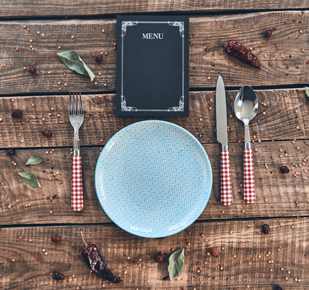 Dinner time. High angle shot of empty plate, fork, spoon, knife and closed menu lying on rustic table Imagens