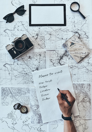 Places I want to visit. Close up top view of man writing down checklist with sunglasses, photo camera, compass, magnifying glass and passport lying on map around