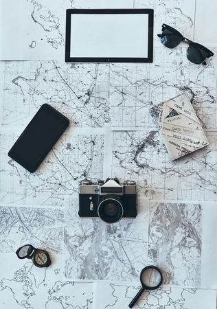 Thing you need in journey. High angle shot of sunglasses, photo camera, compass, magnifying glass, smart phone and passport lying on map