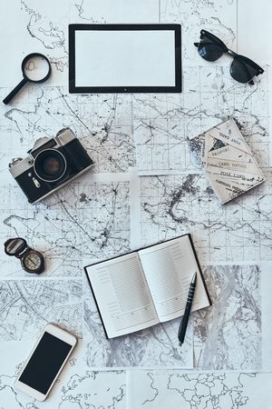 Just travel. High angle shot of sunglasses, photo camera, compass, magnifying glass, diary, smart phone and passport lying on map