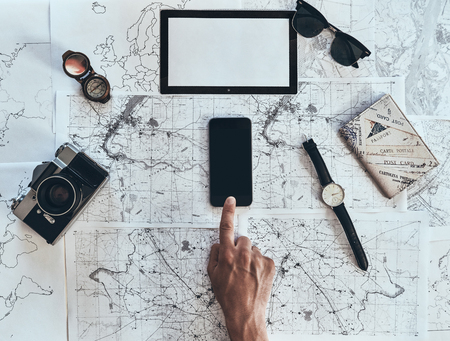 Exploring the world. Close up top view of man using smart phone with sunglasses, photo camera, compass, watch and passport lying on map around Imagens
