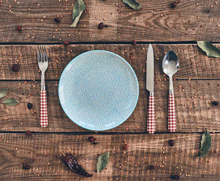 Time for dinner! High angle shot of empty plate, fork, spoon, knife lying on rustic table