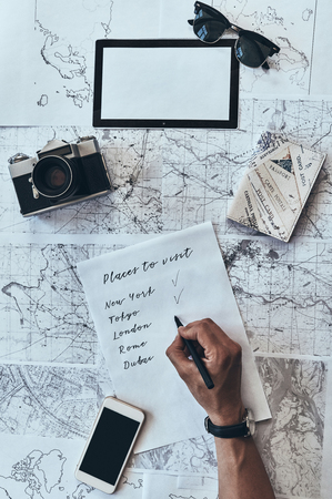 Traveling around the world. Close up top view of man writing down checklist with sunglasses, photo camera, smart phone, passport lying on map around