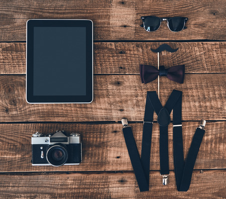 Modern elegance. High angle shot of digital tablet, photo camera, suspenders, prop, bow tie and eyewear lying on wooden desk Imagens