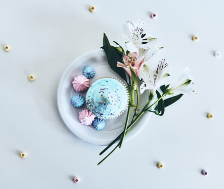 Delicious. High angle shot of cupcake and flowers against white background