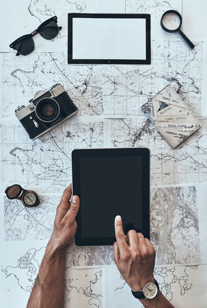 Planning journey. Close up top view of man using digital tablet with sunglasses, photo camera, compass, magnifying glass and passport lying on map around