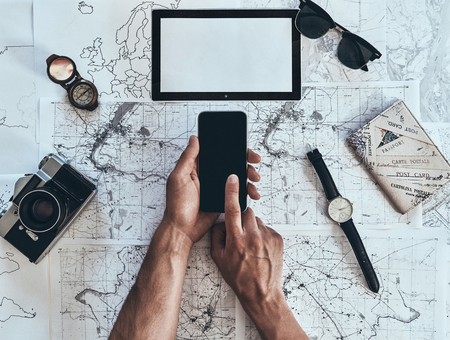 Ready to see the world. Close up top view of man using smart phone with sunglasses, photo camera, compass, watch and passport lying on map around