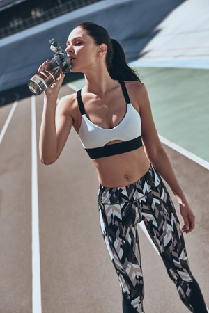 Hydrating. Young woman in sports clothing drinking water while standing on the running track outdoors