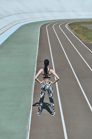 Queen of the track. Top rear view of young woman in sports clothing keeping hands on hips while standing on the running track