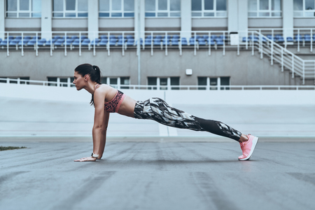 Working hard. Beautiful young woman in sports clothing keeping plank position while exercising outdoors Stock fotó