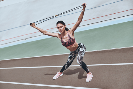 Determined to win. Beautiful young woman in sports clothing exercising using resistance band while standing on the running track outdoors